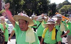 上野千里前全国酪農協会会長(写真左)も拳を振り上げ訴求。広島の一酪農家としてTPP反対を叫ぶ。右は広島を率いる藤岡委員長。