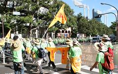 STOP TPP」「TPP参加Mow(猛)反対」のプリントトレーナーをポールにまきつけ都内を行進。