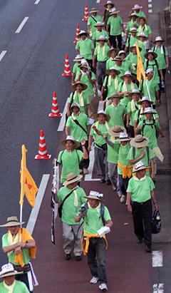 拡声器でシュプレヒコールを叫ぶ西中参事に次いで進む広島デモ隊