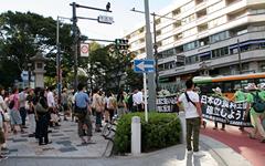 明治神宮前を歩くデモ隊に関心を寄せる多くの人だかり。